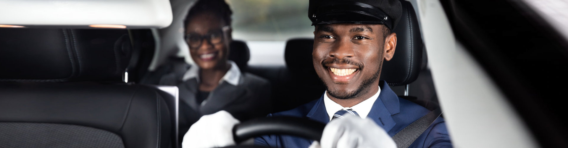 african man and woman smiling inside the car