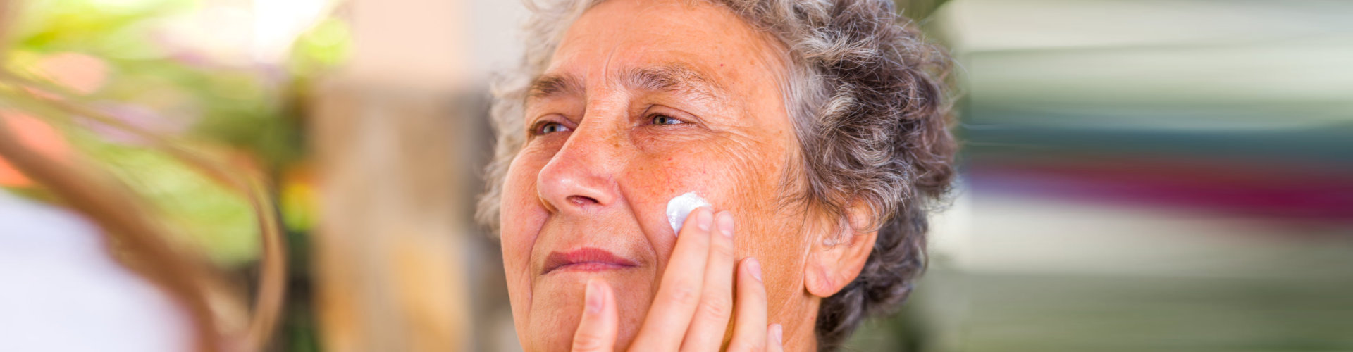 elderly woman face rubbed with cream